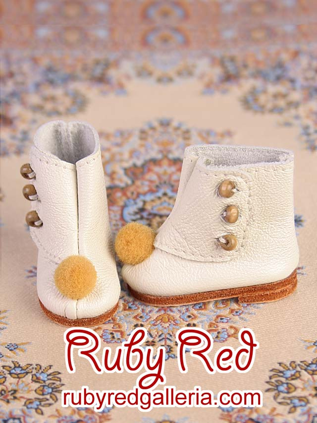White leather booties with pom pom